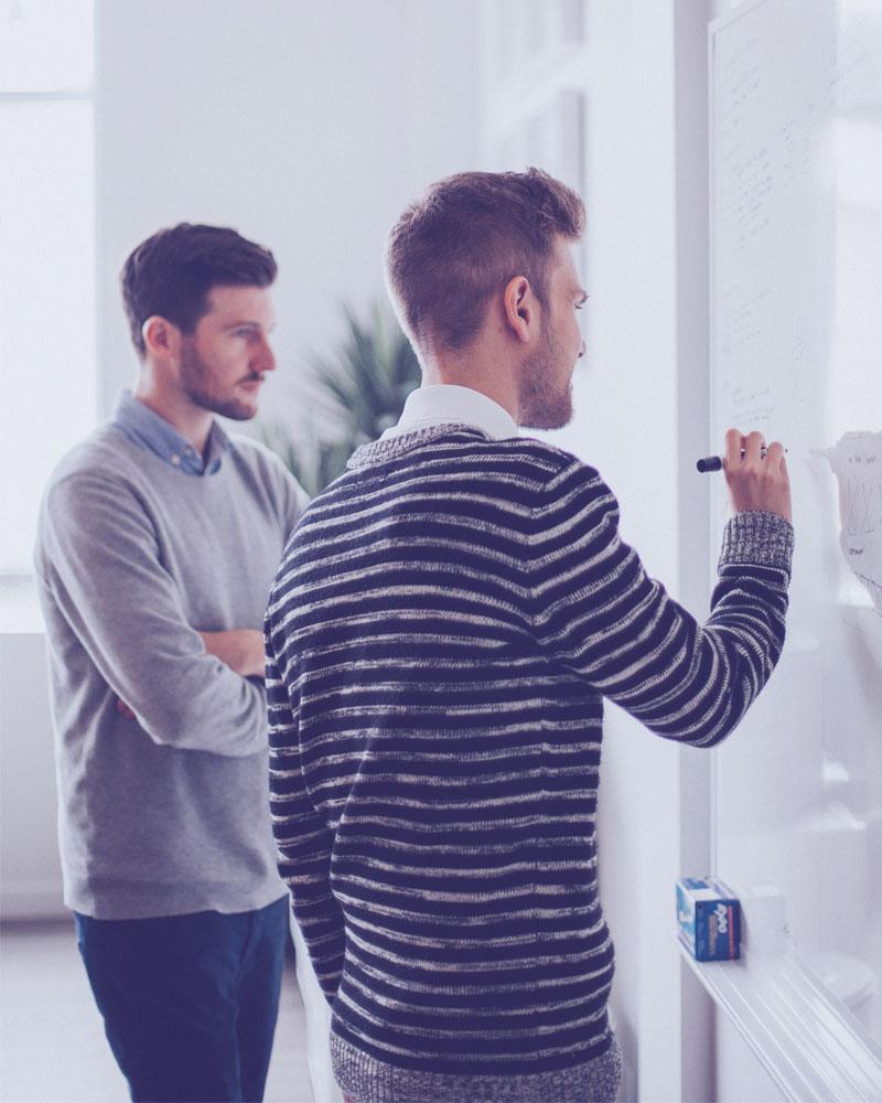 Kaksi miestä suunnittelevat käyttöliittymää.