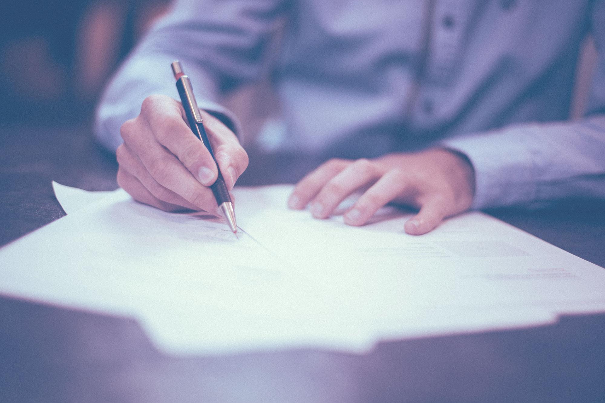 Mies allekirjoittaa papereita.